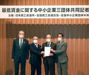 最低賃金の現状維持を求める要望書を手にする日本商工会議所の三村明夫会頭(右から2人目)ら=15日午後、東京都千代田区