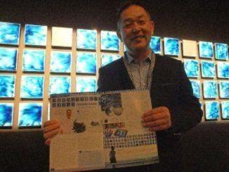 Planete JAPONの記事を手にする金子氏。背景は作品の「サイレント・ブルーウォール」