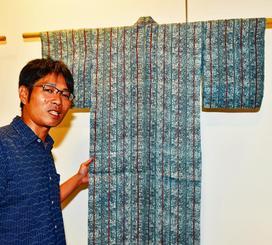 展示された祖父城間栄喜さんの作品に、思いをはせる孫の栄市さん