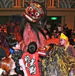 客席を練り歩き、観客を沸かせた那覇市の波上宮獅子舞=25日、うるま市民芸術劇場(長崎健一撮影)