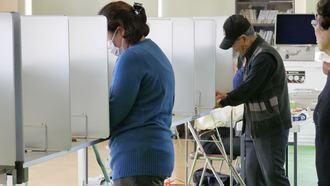 投票用紙に候補者名を書き込む有権者=16日午前、うるま市の投票所
