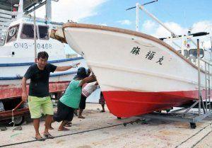 台風襲来に備え、漁船を陸揚げする漁業者ら=6日、石垣市・登野城漁港