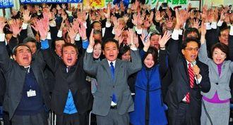 2期目の当選が確実となり、支持者と万歳三唱をする佐喜真淳氏(中央)=24日午後9時17分、宜野湾市野嵩の選対事務所