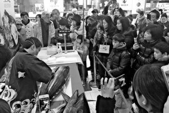 沖縄県産マグロの解体ショーに見入る中国人客=上海・静安区