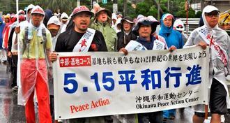 雨の中、基地反対の声を上げて行進する参加者=13日正午、北中城村瑞慶覧