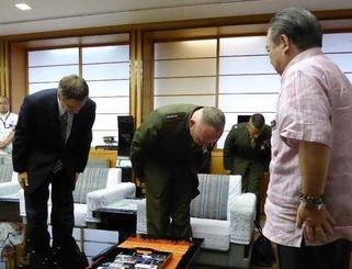 安慶田光男副知事(右)に頭を下げるニコルソン四軍調整官(中央)とエレンライク総領事=20日午後、県庁