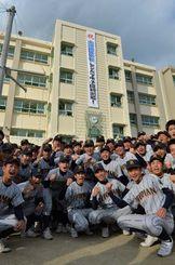 センバツ出場を祝う垂れ幕の前で大会に向け気合を入れる糸満高校野球部員=23日午後、糸満高校