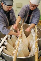 日本酒をしぼる袋をチェックする久保田酒造の担当者=21日、相模原市
