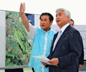市役所の屋上で佐喜真淳市長(左)から普天間飛行場の説明を受ける中谷元・防衛相=9日、宜野湾市役所