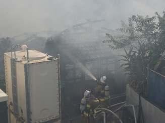 那覇市三原の火災現場で消火活動をする消防隊員7日午後