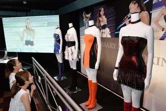 安室奈美恵さんのステージ衣装やライブ映像を見詰める関係者=1日、沖縄市・プラザハウスショッピングセンター(古謝克公撮影)