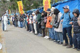 新基地建設反対を訴える集会で、米軍基地に向かって腕を組んで抗議する市民ら=10日午後0時20分、キャンプ・シュワブのゲート前