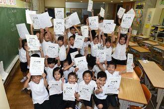 よい子のあゆみとがんばり賞を受け取り、笑顔いっぱいの児童=17日午前10時前、宜野湾市の大謝名小学校