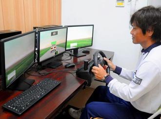 高次脳機能障害の患者の運転能力を評価するサポートソフトを説明する技能検定員の仲原英久さん(右)。操作反応の速さや正確さをはかることができる=南風原町・津嘉山自動車学校