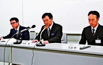混入の経緯や対応について説明する狩俣教育長(中央)=11日、沖縄市役所