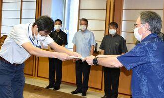 高山義浩医師(左)に県政策参与の委嘱状を交付する玉城デニー知事=22日、県庁
