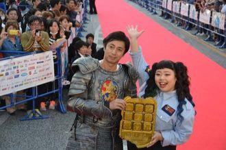 報道陣の呼び掛けに手を挙げて応える芸人の渡辺直美さん(右)と、チュートリアルの徳井義実さん=28日、沖縄市のゲート通り