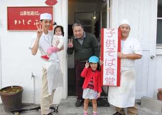 子どもそば食堂で居場所づくりに取り組む池原賢さん(中央)らスタッフ=「いしぐふー」港川店