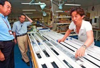 伊平屋沖の熱水鉱床から採取した物質を説明するJAMSTEC海底資源研究開発センターの高井研上席研究員(右)=26日、中城新港地区に停泊中の地球深部探査船「ちきゅう」