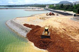 辺野古新基地建設工事が再開。米軍キャンプ・シュワブ沿岸部の埋め立て区域に、土砂を海に投入するブルドーザー=12日午後2時22分、名護市辺野古(小型無人機で撮影)