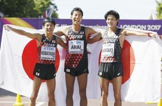 男子50キロ競歩でゴール後、日の丸をまといポーズをとる(左から)銅メダルの小林快、銀メダルの荒井広宙、5位の丸尾知司=ロンドン(共同)