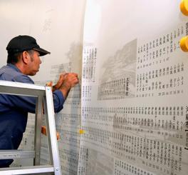 対馬丸犠牲者の刻銘板を新しいシートに貼り替える作業員=那覇市若狭、対馬丸記念館