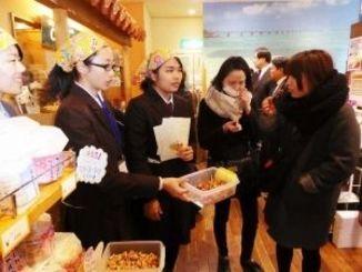 西原町でつくられた商品の販売体験をする高校生ら=5日、東京・銀座わしたショップ