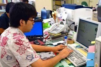 マイナンバー法施行に関連して新たに構築した電子メールやインターネットに使うシステムへの接続作業をする職員=5日、恩納村役場