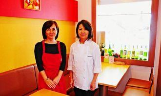 温かい色でまとめた店内で。オーナーの穐山由香さん(左)と料理を担当する母親の真喜志エミ子さん=豊見城市宜保