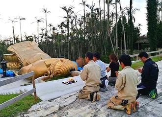 脱魂式で像に手を合わせる関係者=7日、沖縄市・東南植物楽園(同園提供)