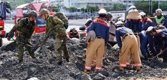 大地震発生を想定し、行方不明者を探す訓練をする消防隊員や自衛隊員=5日、北中城村の熱田漁港