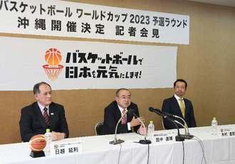 W杯の沖縄開催決定で記者会見する日本バスケットボール協会の田中道博専務理事(中央)ら=11日、県庁