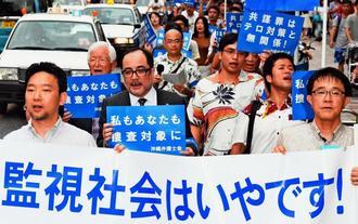 「共謀罪」反対を訴え横断幕やプラカードを手にデモ行進する弁護士ら=12日午後、那覇市牧志