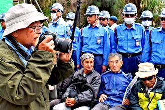 座り込む人たちが強制排除される様子を撮影する石川文洋さん(左)=13日、名護市辺野古