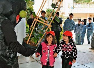 ホウライカガミの鉢を着ぐるみから受け取る子どもたち=うるま市・中部農林高校