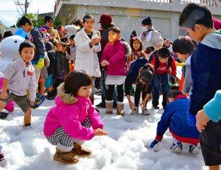 雪だるまを作って遊ぶ子どもたち=嘉手納町・新町通り