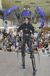 「スケルトニクス・アライブ」ロボットのデモンストレーションで、歩行や細かな動きをする手に見入る来場者=24日午後、那覇市・県立武道館アリーナ