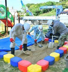 米軍の泡消火剤が付着したとみられる遊び場の砂を除去する作業員=18日午前、宜野湾市・第2さつき認定こども園