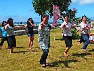 ギネス記録に挑戦するフラを奉納する参加者ら=1日、宮古島市伊良部の佐和田の浜前