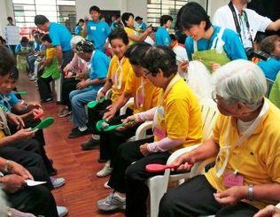 しゃもじでお手玉運びのゲームを楽しむ3地区のデイサービス利用者のお年寄りたち=サンフアン日本人移住地