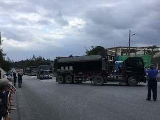 市民が抗議行動を展開する中、新基地建設用とみられる資材を積んだ工事車両が車列を組んで次々と基地内へ入った=10日午前9時すぎ、名護市辺野古の米軍キャンプ・シュワブゲート前