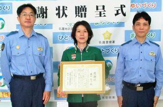 名護署の知念克幸署長(左)から感謝状を受け取る鎌田玲子さん(中央)。山城純一生活安全課長=1日、名護署