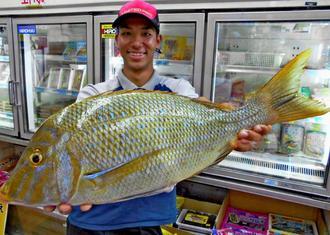 恩納村海岸で62センチ、3キロのタマンを釣った當山正宙さん=10月6日