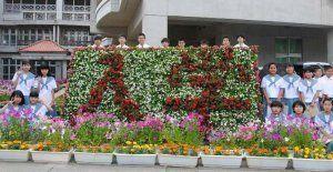 寄贈された花で作られた花文字を囲み、期待と不安で胸いっぱいの新入生たち=8日、浦添市・神森中学校