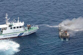 炎上するダイビング船の消化活動にあたる海保=17日、竹富町黒島沖(第11管区海上保安本部石垣航空基地提供)