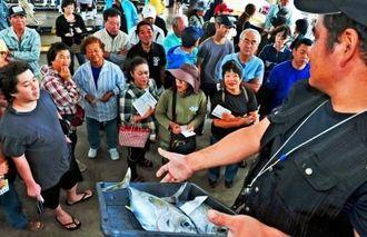知念漁協が初めて開いた一般参加型セリ。セリ長(右)が手に持った魚を見つめ、品定めする一般参加者たち=3日午前、南城市・知念漁業協組合のセリ場