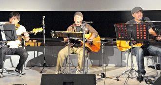 伸びやかな歌声を披露する、のひなひろしさん(中央)ら出演者=9日、「シネマパニック宮古島」