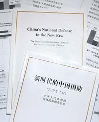 中国政府が発表した国防白書「新時代の中国国防」の中国語版(手前)と英語版(共同)