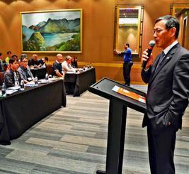 在ニュージーランド日本大使館の高田稔久特命全権大使(右)の講話に耳を傾ける視察団のメンバーら=オークランド内のホテル