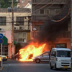 軽自動車に乗っていた2人が車外に出た後、出火し炎上する軽自動車=29日午後、那覇市楚辺2丁目の国道330号(上原愛子さん撮影)